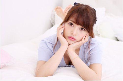 ベッドの上で頬杖をついている女性