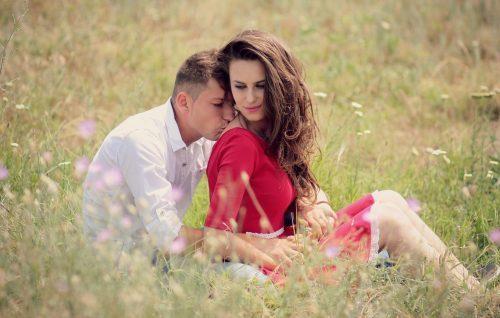 女性の背中にキスをする男性