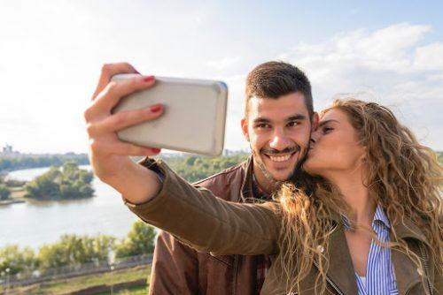 男性にキスをしながらセルフィーを撮る女性