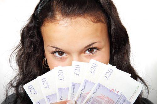 お金を広げている女性