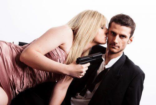 男性の首元に銃を突き付ける女性