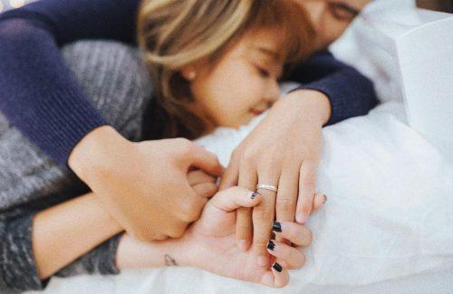 ベッドの上で手を絡める男女