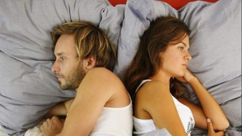 ベッドの上で背中を向ける男女