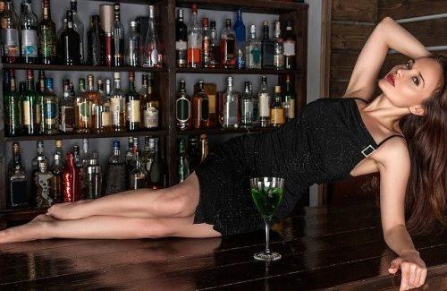 バーカウンターの上に寝る女性