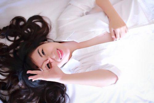ベッドで寝転がり笑う女性